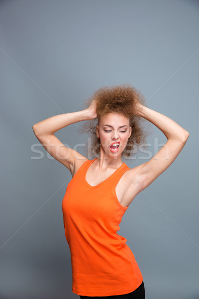 Amusing confident young woman posing and making a grimace Stock photo © deandrobot