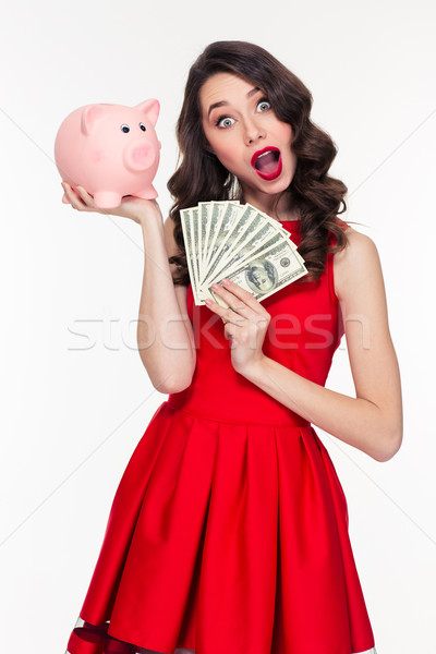 Amazed beautiful curly woman holding pink piggy bank and money Stock photo © deandrobot