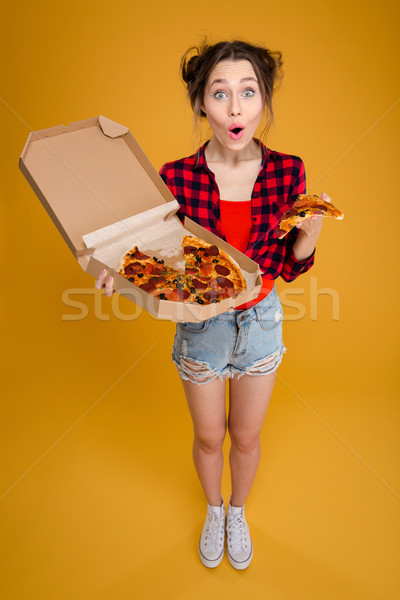 Surprised happy pretty young woman standing and holding pizza Stock photo © deandrobot