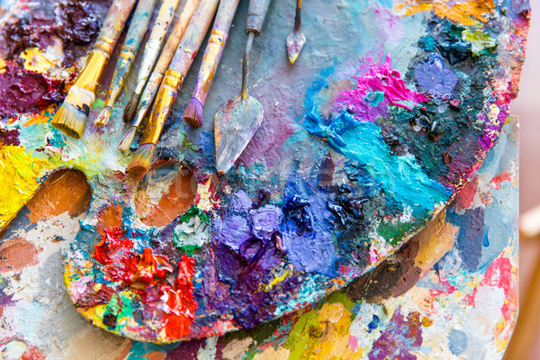 Closeup of art palette with colorful mixed paints and paintbrushed  Stock photo © deandrobot