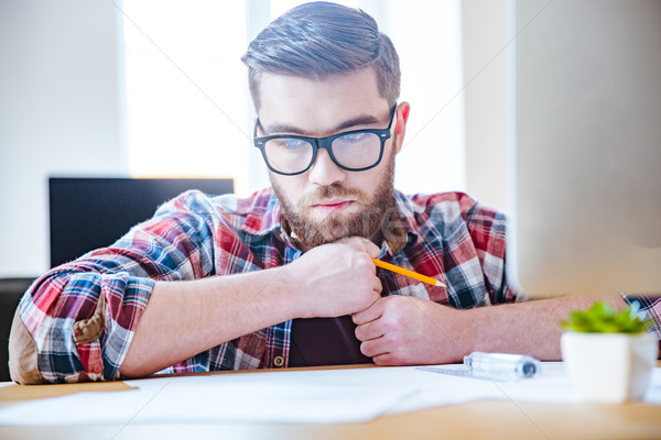 Pensive bearded engineer sitting at the table and creating blueprint Stock photo © deandrobot
