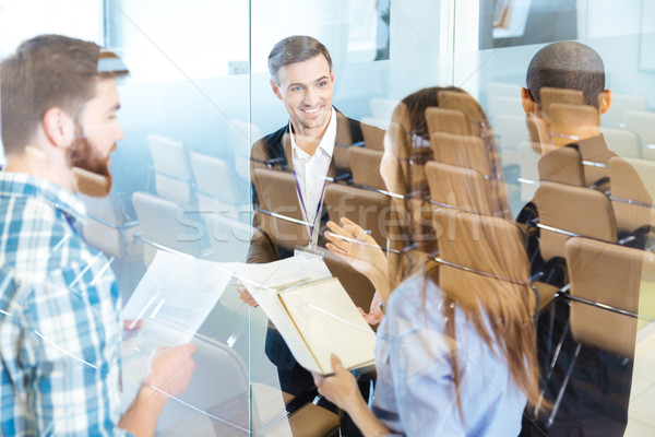 Group of smiling young business people discussing new ideas  Stock photo © deandrobot
