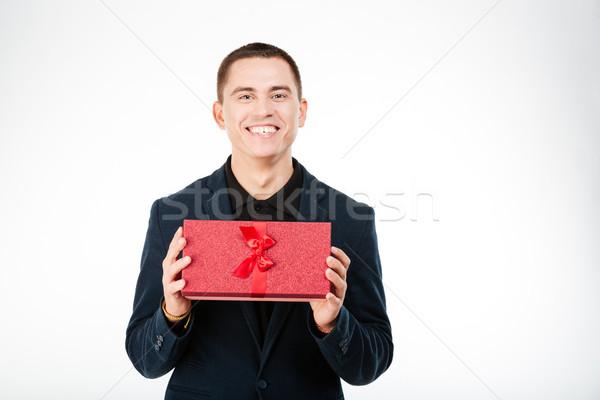 Happy businessman holding present box  Stock photo © deandrobot