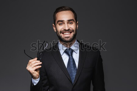 Smiling attractive businessman in black suit standing with hands folded  Stock photo © deandrobot
