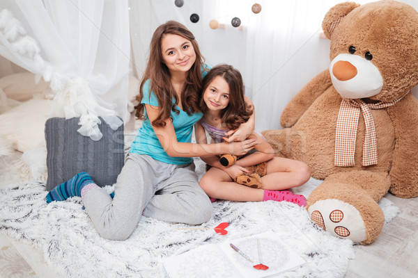 Two happy sisters sitting and hugging in children room  Stock photo © deandrobot