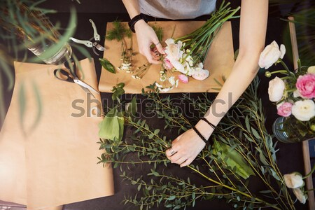 Hands of woman florist creating flower bouquet on table Stock photo © deandrobot