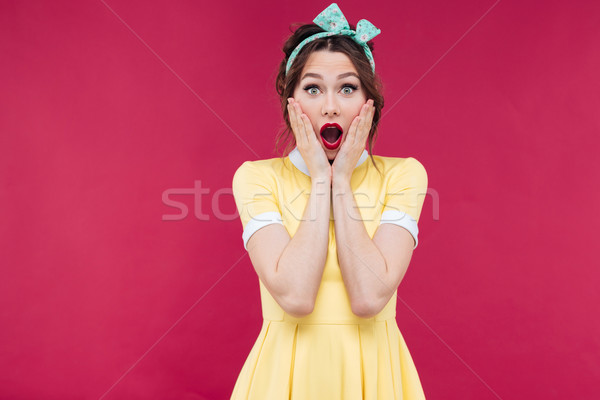 Amazed pinup girl in yellow dress standing with mouth opened Stock photo © deandrobot
