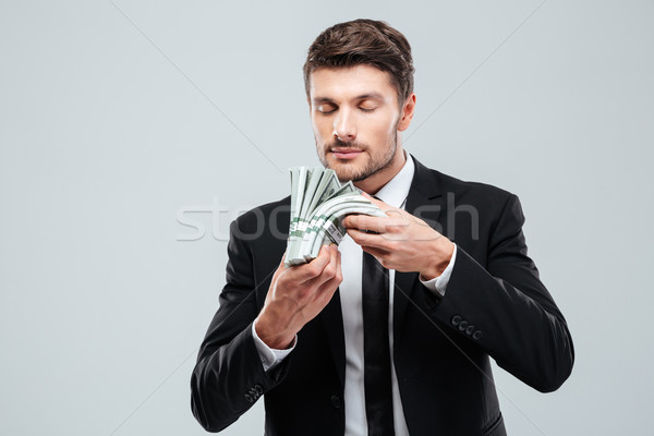 Handsome young businessman holding and smelling money Stock photo © deandrobot