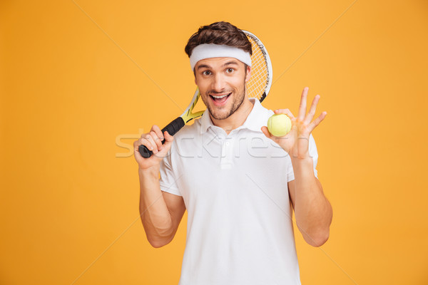 Cheerful young man tennis player holding ball and racket Stock photo © deandrobot