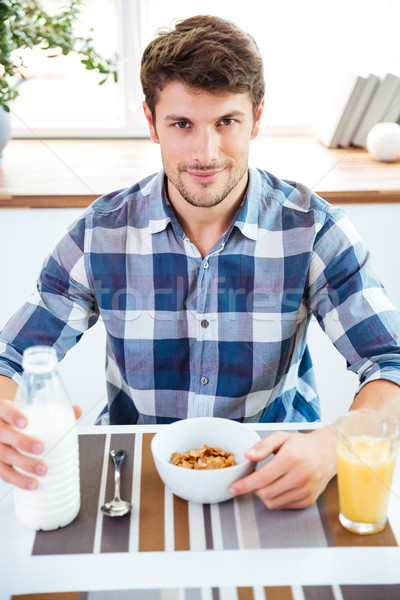 Man sitting and eating cereals with milk on the kitchen Stock photo © deandrobot