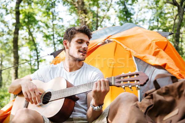 Smiling young man tourist sitting and playing guitar in forest Stock photo © deandrobot