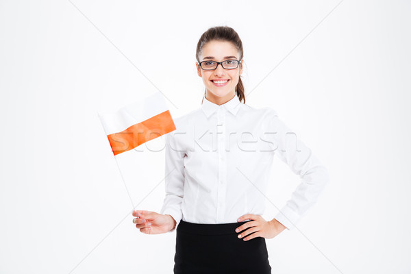 Happy charming young businesswoman smiling and holding flag of Poland Stock photo © deandrobot