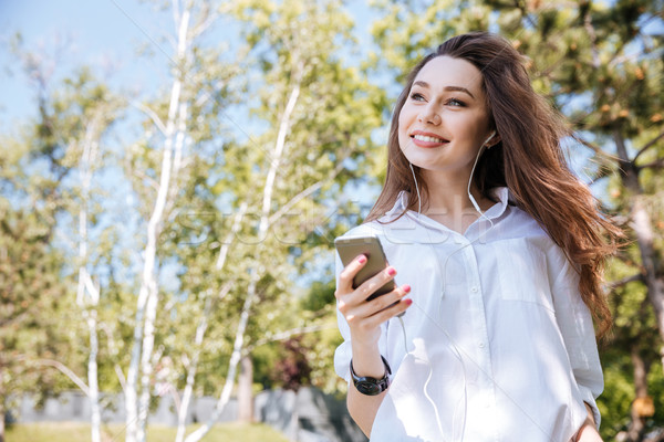 Young happy woman listening music at the park Stock photo © deandrobot