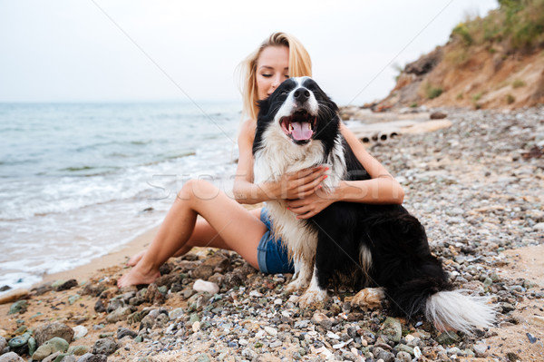 Happy woman hugging her dog on the beach Stock photo © deandrobot