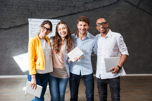 Multiethnic group of happy young business people standing in office Stock photo © deandrobot
