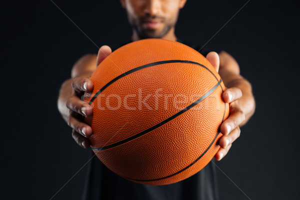 Cropped image of a focused african basketball player giving ball Stock photo © deandrobot