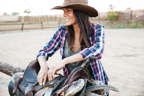 Cheerful young woman cowgirl preparing saddle for riding horse Stock photo © deandrobot