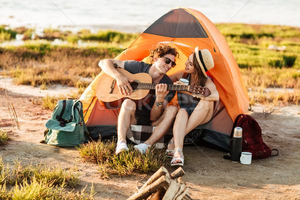 Człowiek gry gitara posiedzenia kemping namiot Zdjęcia stock © deandrobot