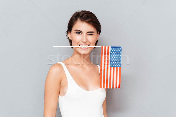 Happy young woman holding USA flag in teeth and winking Stock photo © deandrobot
