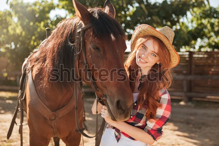 Cheerful woman cowgirl in hat with her horse in village Stock photo © deandrobot