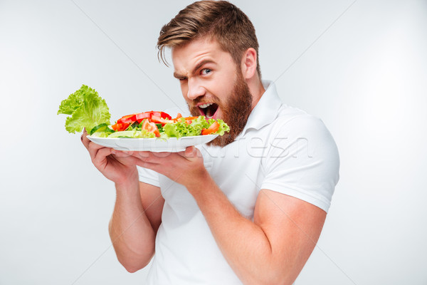 Young hungry bearded man eating salad Stock photo © deandrobot