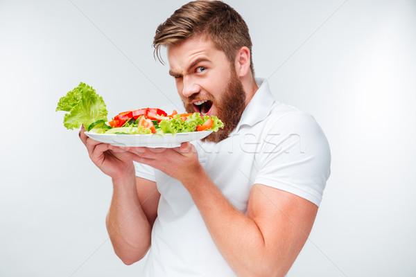 Jonge hongerig bebaarde man eten salade Stockfoto © deandrobot