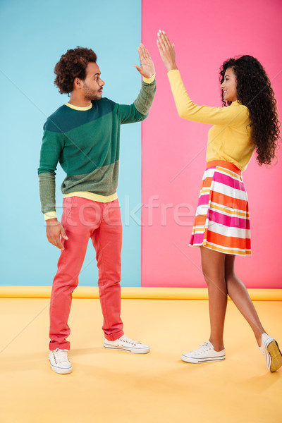 Beautiful african young couple standing and giving high five Stock photo © deandrobot