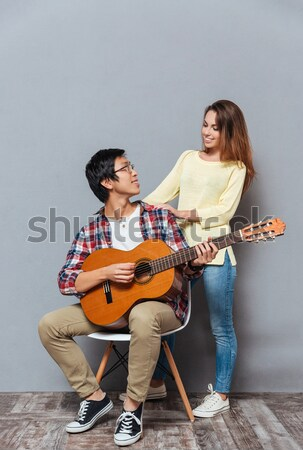 Full length portrait of a happy interracial couple playing guitar Stock photo © deandrobot