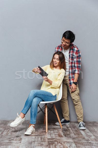 Young interracial couple using digital tablet Stock photo © deandrobot