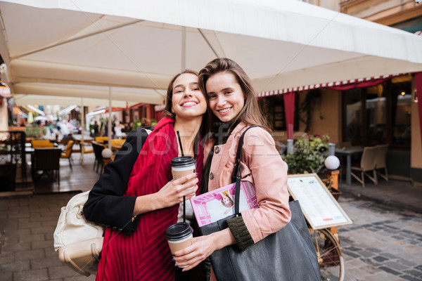 Two happy women with takeaway coffee standing in old town Stock photo © deandrobot
