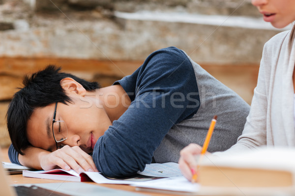 Asian man in glasses sleeping on the lesson Stock photo © deandrobot