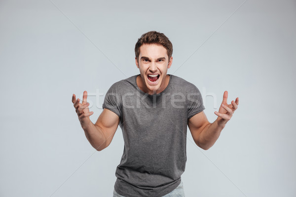 Portrait of an excited young man with both hands up Stock photo © deandrobot