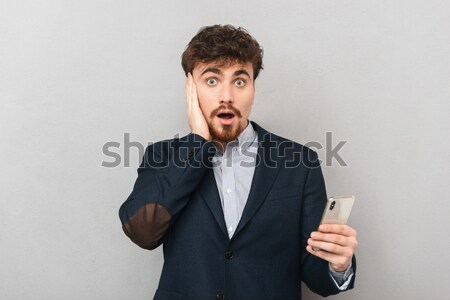 Portrait of a man holding condom and looking at camera Stock photo © deandrobot