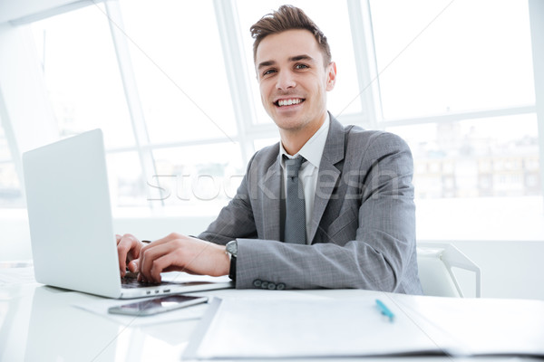 Smiling business man sitting by the table with laptop Stock photo © deandrobot