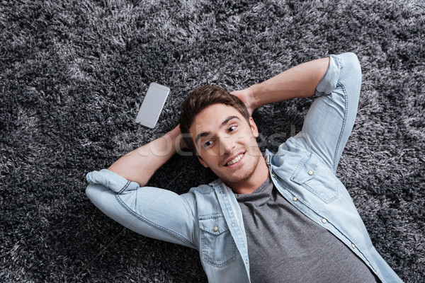 Smiling casual man lying on the carpet with mobile phone Stock photo © deandrobot