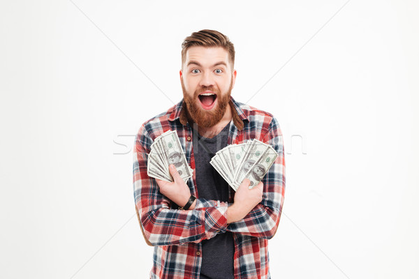 Happy young bearded man in plaid shirt holding dollar bills Stock photo © deandrobot