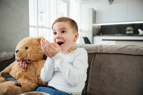 Surprised boy on sofa with teddy bear watching TV Stock photo © deandrobot