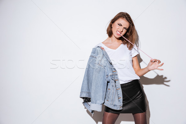 Woman dressed in jeans jacket stretching bubble gum. Stock photo © deandrobot
