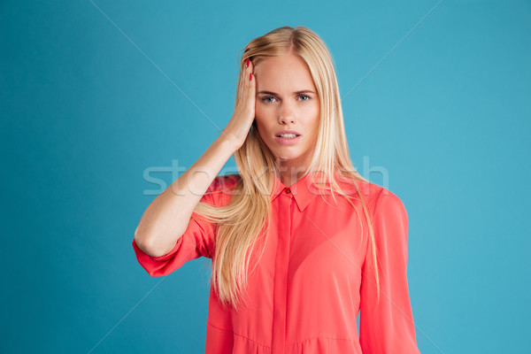 Portrait of a blonde woman with headache in red dress Stock photo © deandrobot