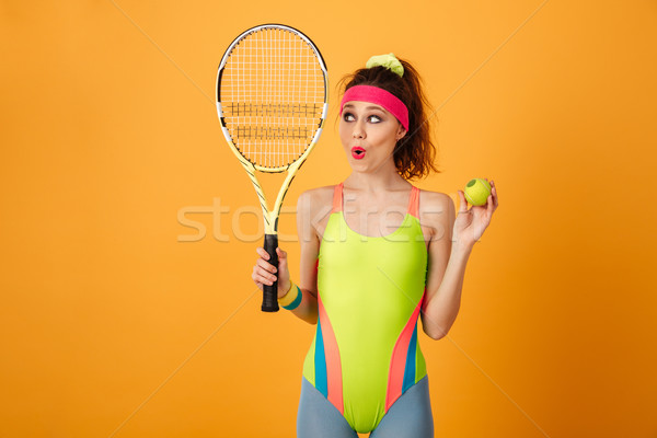 Cute amazed young fitness woman holding tennis racket and ball Stock photo © deandrobot