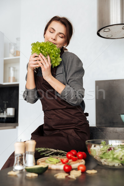 Woman smells lettuce leaves and cooking Stock photo © deandrobot