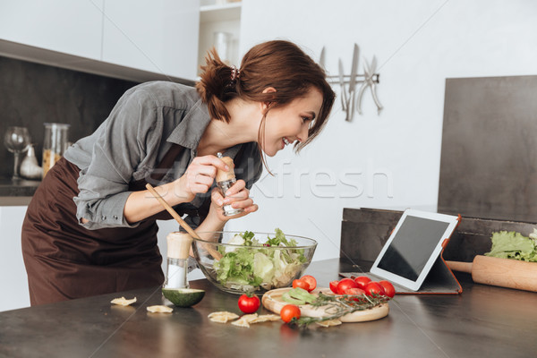 Lady cooking salad in kitchen using tablet Stock photo © deandrobot