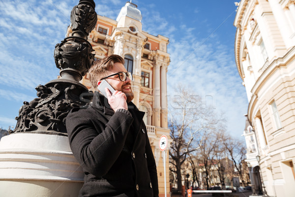 Sonriendo hombre abrigo hablar teléfono calle Foto stock © deandrobot