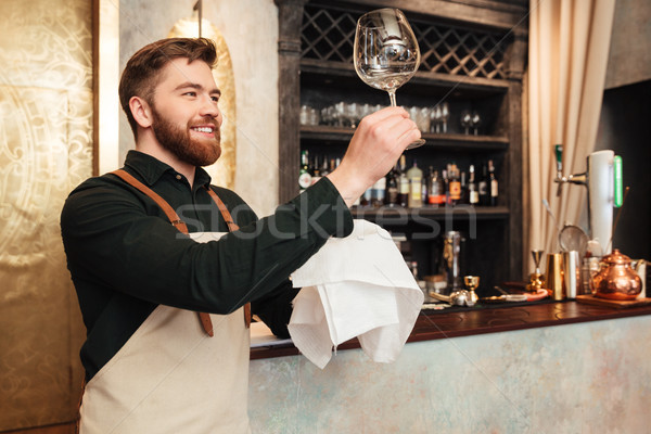 Attractive young bearded man bartender standing in cafe Stock photo © deandrobot