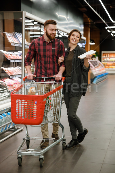 Happy loving couple in supermarket choosing products. Stock photo © deandrobot