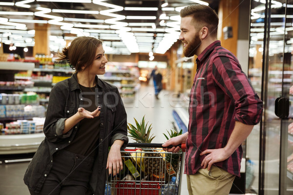 Happy loving couple talking in supermarket with shopping trolley Stock photo © deandrobot