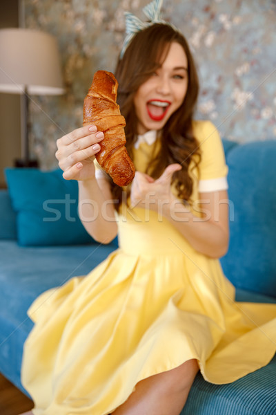 Happy young pin-up lady eating croissant while make thumbs up Stock photo © deandrobot
