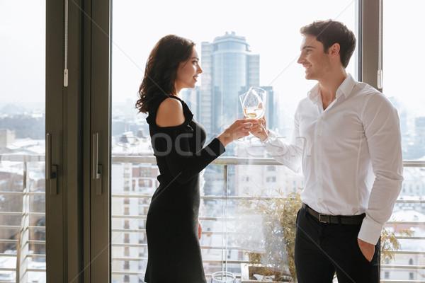Happy loving couple standing near window drinking alcohol Stock photo © deandrobot