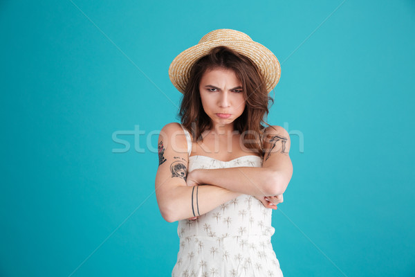 Portrait of grumpy moody girl in straw hat standing Stock photo © deandrobot