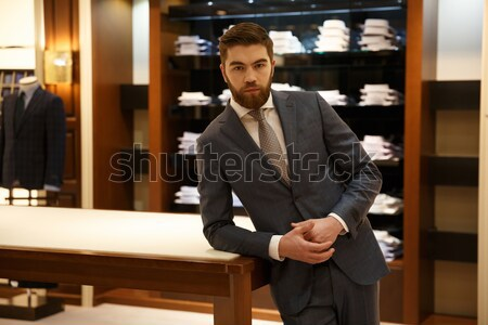 Calm man standing near the table with crossed arms Stock photo © deandrobot